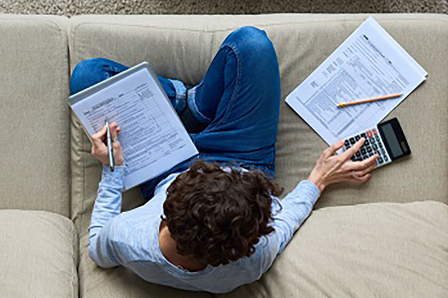 Person Doing Taxes on Couch